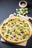 Delicious mushroom quiche on black. Background with knife Royalty Free Stock Photography