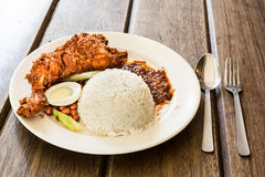 Delicious Nasi Lemak with fried chicken on wooden table Royalty Free Stock Photos