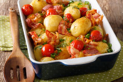 Delicious new potatoes baked with bacon, herbs and tomatoes clos Royalty Free Stock Photography
