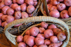 Delicious new potatoes in baskets on wood table Stock Photo