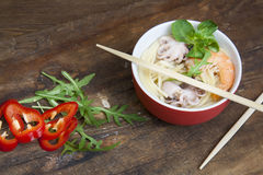 Delicious noodles with shrimp and octopus on a plate in wooden background Royalty Free Stock Images