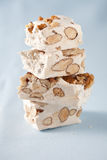 Delicious nougat. Few pieces of nougat stacked together on light blue background Royalty Free Stock Photos