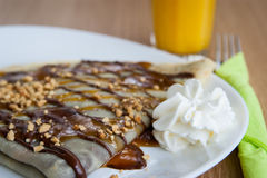 Delicious nougat, caramel and peanuts pancake decorated with whi Stock Photo