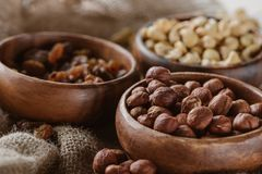 Delicious nuts in wooden bowls. On sackcloth background stock photo