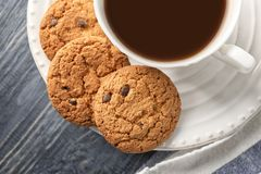 Delicious oatmeal cookies with chocolate chips and cup. Of coffee on plate Royalty Free Stock Photo