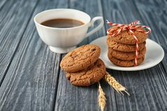 Delicious oatmeal cookies with chocolate chips. And cup of coffee on wooden table Royalty Free Stock Image