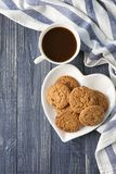 Delicious oatmeal cookies with chocolate chips. And cup of coffee on table Stock Image