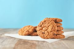 Delicious oatmeal cookies with chocolate chips. On wooden table against color background Royalty Free Stock Image