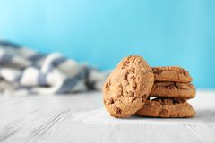 Delicious oatmeal cookies with chocolate chips. On wooden table against color background Stock Photos