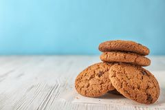Delicious oatmeal cookies with chocolate chips. On wooden table against color background royalty free stock images