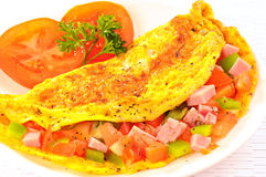 Delicious omelet with tomato, pepper, ham, basil. On a plate Stock Photography