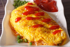 Delicious omelette with rice, green peas and ketchup close-up Royalty Free Stock Images
