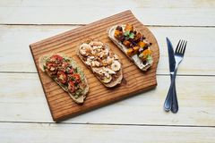 Delicious open faced sandwiches sitting with cutlery on a table Stock Photography