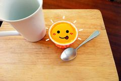 Delicious Orange Cupcake A Smile Face with Glass and Spoon Wood on Wooden Salver Background. Great for Any Use Royalty Free Stock Photography