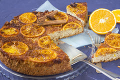Delicious orange pie. With cinnamon and star aniseed on napkin with little fork and fresh orange Stock Photography