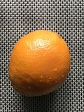 A delicious orange sits ripe on a table just waiting to be devoured Royalty Free Stock Image