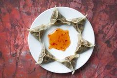 Delicious oriental Dim Sum dumplings on white plate on art baackground. Delicious oriental Dim Sum dumplings homemade royalty free stock photography
