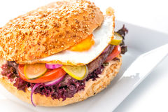 Delicious original american hamburger with grilled beef, egg and vegetables on white plate, snack or lunch, product photography fo Stock Photos