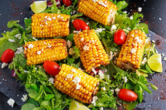 Delicious oven cooked Corn with feta cheese, paprika, lime, vegetables. Stock Photography
