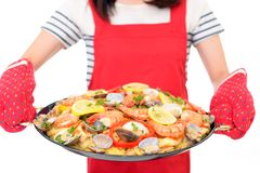 Delicious paella in pan. Woman holding a paella in pan stock photos