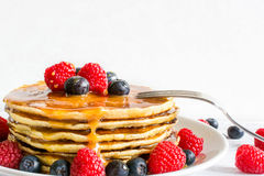 Delicious pancakes with berries and caramel sauce with fork. Over white wooden table. soft focus. close up Stock Photo
