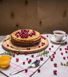 Delicious pancakes with berries and a cup of tea, honey and spoon wooden rustic background close up Stock Photos