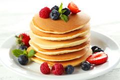 Delicious pancakes with berries on white wooden background. Royalty Free Stock Photos