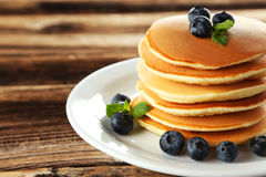 Delicious pancakes with blueberries on brown wooden background Royalty Free Stock Photo