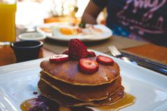 Delicious breakfast of pancakes with syrup and strawberries. stock photography