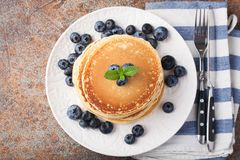 Delicious pancakes close up, with fresh blueberries on rusty background. Top view with copy space.  Royalty Free Stock Images
