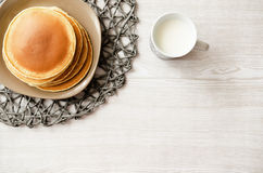 Delicious pancakes and cup of milk on wooden table Stock Images