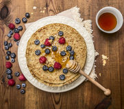 Delicious pancakes with fresh berries with honey, almonds cup of tea with honey spoon on white plate with napkin on wooden rustic Stock Images