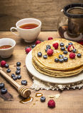 Delicious pancakes with fresh berries on a white plate with honey spoon and cup of tea on wooden background close up Royalty Free Stock Images