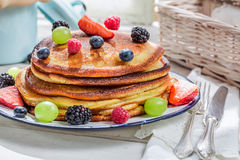 Delicious pancakes with fresh fruits for breakfast. On old wooden table stock image