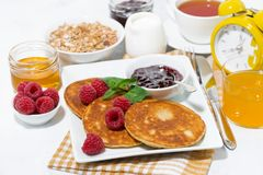 Delicious pancakes with fresh raspberries and jam for breakfast. Closeup Stock Photos