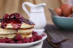 Delicious Pancakes with Fresh Rasperries and Raspberry Sauce. Delicious homemade golden pancakes with fresh raspberries and raspberry syrup. Extreme shallow Stock Images