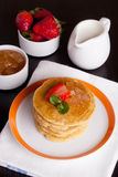 Delicious pancakes with fresh strawberries on a plate and jam. Delicious pancakes with fresh strawberries on a plate, jam and milk, vertical, close-up Royalty Free Stock Image