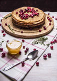 Delicious pancakes, lined hill with cranberries and honey, on a cutting board on a napkin on wooden rustic background close up Royalty Free Stock Image