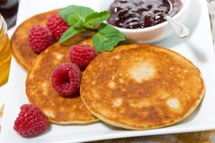 Delicious pancakes with raspberries and jam for breakfast. Closeup horizontal Stock Image