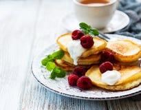 Delicious pancakes with raspberries. On white wooden background Stock Photos
