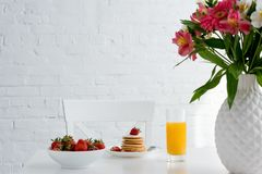 Delicious pancakes with strawberries and orange juice on table with flowers in front of white. Brick wall royalty free stock photos