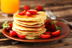 Delicious pancakes with strawberry on brown wooden background Royalty Free Stock Images