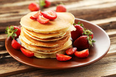 Delicious pancakes with strawberry on brown wooden background Royalty Free Stock Photos