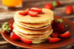 Delicious pancakes with strawberry on brown wooden background Stock Photography