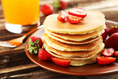 Delicious pancakes with strawberry on brown wooden background Stock Photos