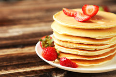 Delicious pancakes with strawberry on brown wooden background Stock Images