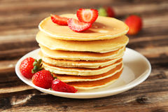 Delicious pancakes with strawberry on brown wooden background Royalty Free Stock Photography