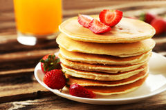 Delicious pancakes with strawberry on brown wooden background Stock Photo