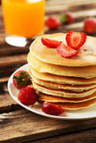 Delicious pancakes with strawberry on brown wooden background Royalty Free Stock Image