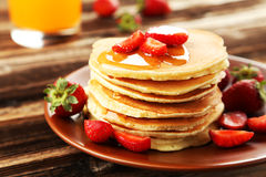 Delicious pancakes with strawberry on brown wooden background. Stock Images